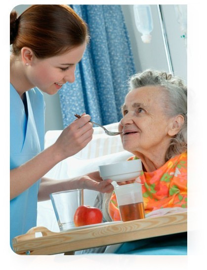 доглядальниця годує літню жінку у пансіонаті