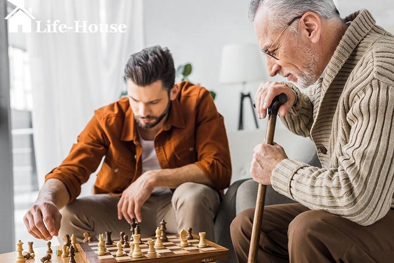 чоловік грає в шахи зі своїм літнім батьком