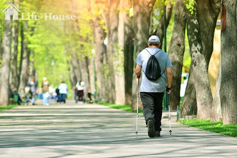 пожилой человек выполняет скандинавскую ходьбу в парке