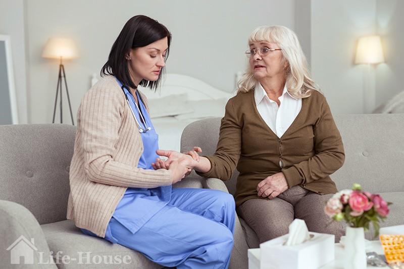 медсестра вимірює пульс літньої жінки