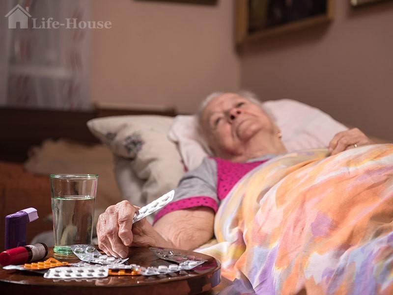 пожилая женщина, лежащая на кровати
