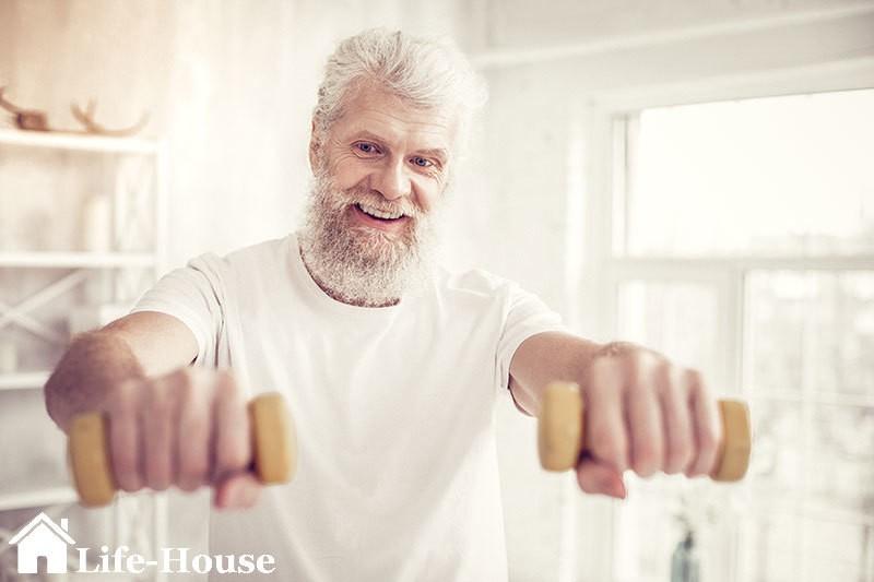 мужчина использует в реабилитационном процессе гантели