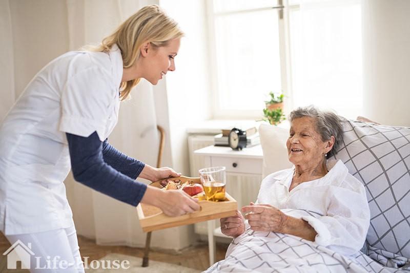 заботливая сиделка помогает с приемом пищи постояльцу дома престарелых