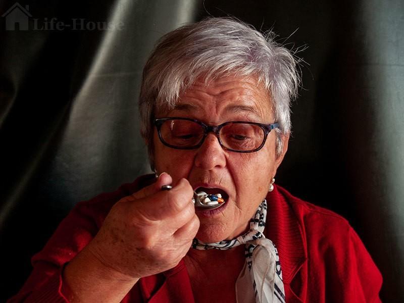 женщина принимает целую ложку таблеток