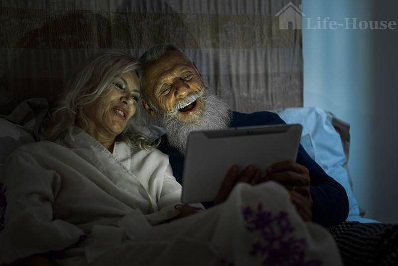 пожилая пара смотрит фильмы в постели перед сном
