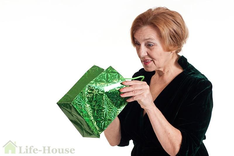 пожилая женщина открывает пакет с подарком
