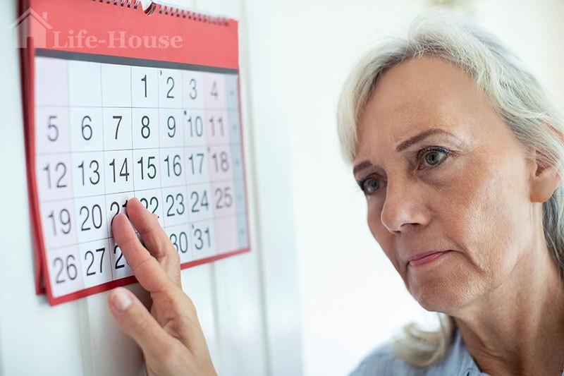 женщина у календаря испытывает проблемы с памятью