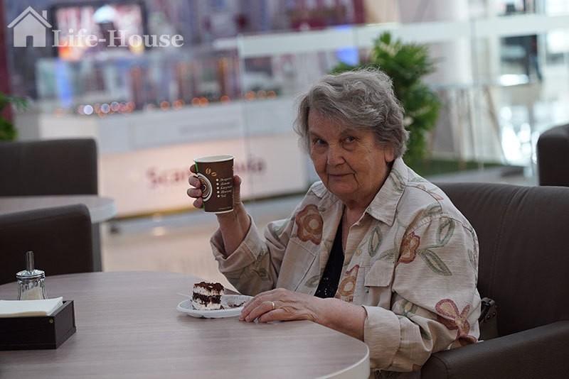пожилая женщина кушает в городском кафе