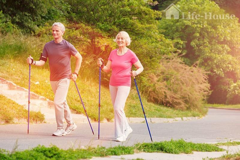 пожилая пара занимается скандинавской ходьбой