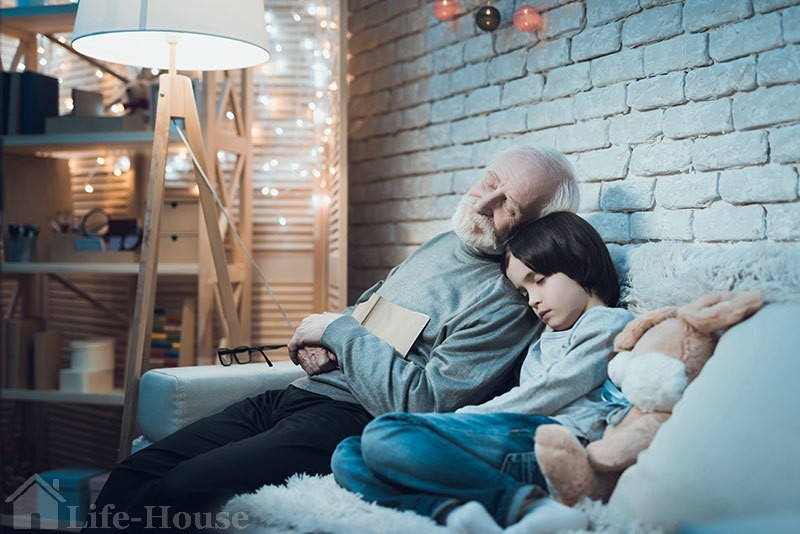 пожилой мужчина дремает, сидя на диване, рядом с внуком