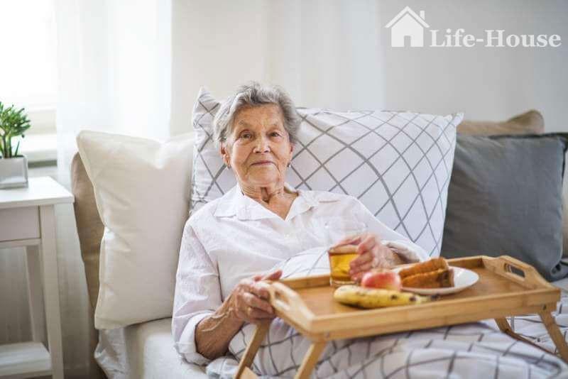 пожилая женщина кушает лежа на кровати