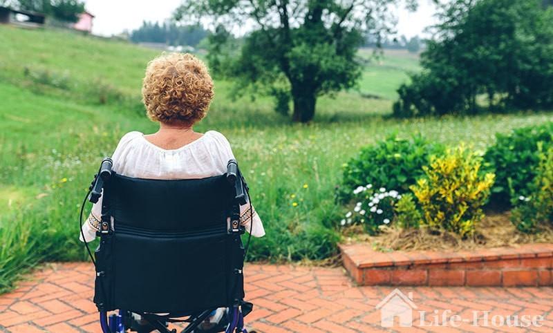 женщина на инвалидном кресле, смотрящая вдаль