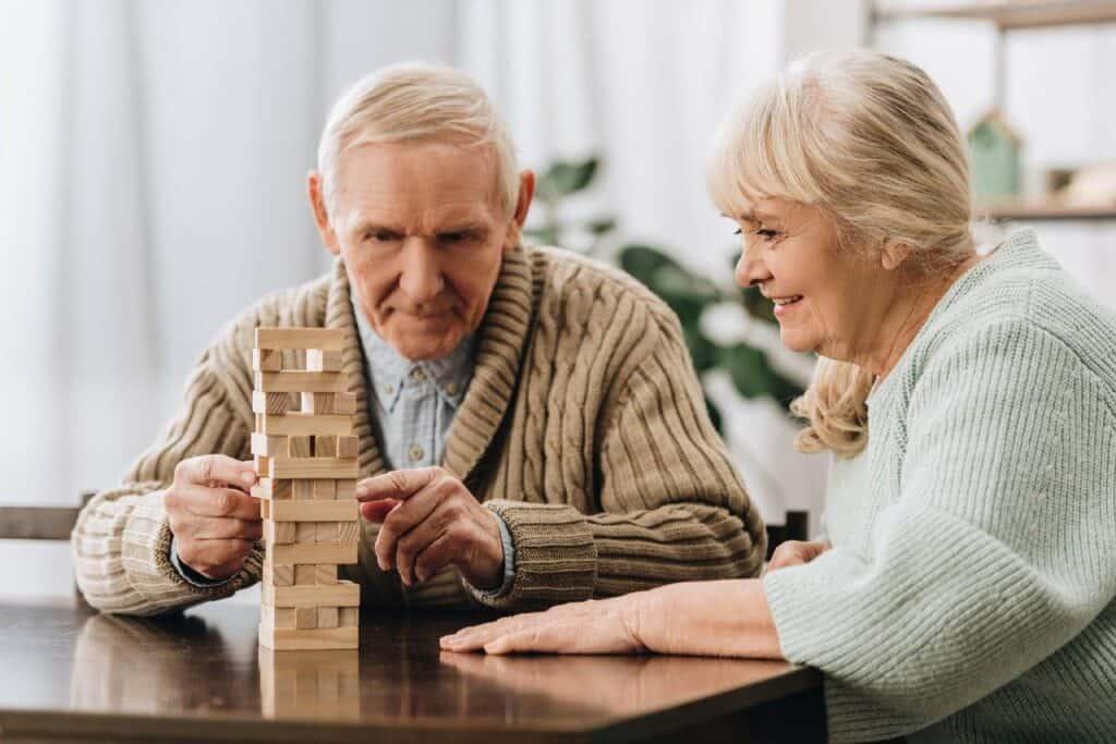 пожилая пара тренирует когнитивные способности, играя в настольную игру